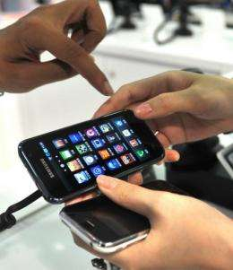 A shopper looks at a smartphone at a shop in Taipei