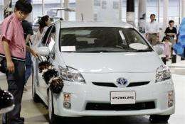 File photo shows a worker dusting a Japanese auto giant Toyota Motor's hybrid Prius