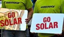 """Activists of the environmental group Greenpeace hold banners reading, """"Go Solar"""" during a demonstration in Rome"""