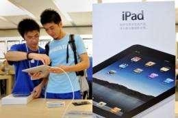 A customer (R) checks an iPad at the Apple store in Shanghai