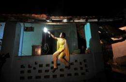 A girl switches on a light powered by solar energy in the village of Morabandar
