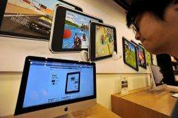 A man looks at monitors displaying the Apple iPad website