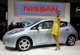 """A model poses next to Nissan's electric  """"Leaf"""" car at the Geneva International Motor Show"""