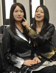 """A model (R) touches the face of a humanoid robot called """"Geminoid-F"""" (L)"""