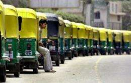 An auto rickshaw driver waits in a queue for his turn to get a refill with Compressed Natural Gas