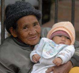 An elderly woman cares for her infant grand-daughter at a market in the mountain town of Sagada, The Philippines