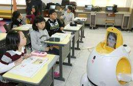 """An English-teaching robot (R), """"Engkey"""", stands in front of children at an elementary school in South Korea"""