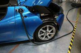 A power cable is seen plugged into a Tesla Roadster