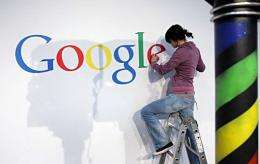 A stand builder fixes a logo at the Google stand at the CeBit 2010 exhibition