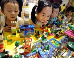 Japanese children look at their work made by LEGO bricks as part of the Dream City building event in Tokyo