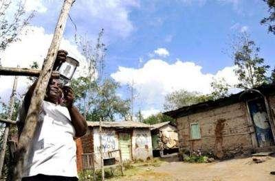 Jeniffer David hangs her solar-lamp outside her house at Chumbi village, some 50 km southeast of Nairobi