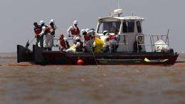 Oil spill cleanup workers adjust an oil boom at South Pass near the mouth of the Mississippi River
