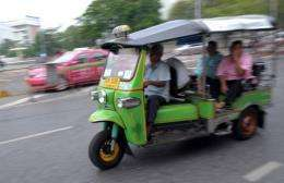Passengers are transported on a 'Tuk-tuk' in central Bangkok