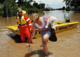 Robyn Russell (R) and her dog 'Elle' disembark from a rescue boat