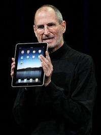 Steve Jobs holds up the new iPad