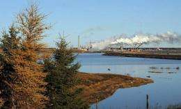 The Syncrude oil sands extraction facility is seen behind a lake in Alberta Province, Canada in 2009