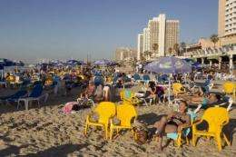 Unseasonally warm weather in Tel Aviv on Monday tempted people onto the city's Mediterranean beach